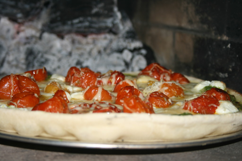 Pesto Pizza with Roasted Tomatoes and Caramelized Onions in Pizza Oven